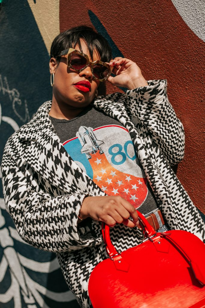 Black woman in red lipstick and coat poses for photo