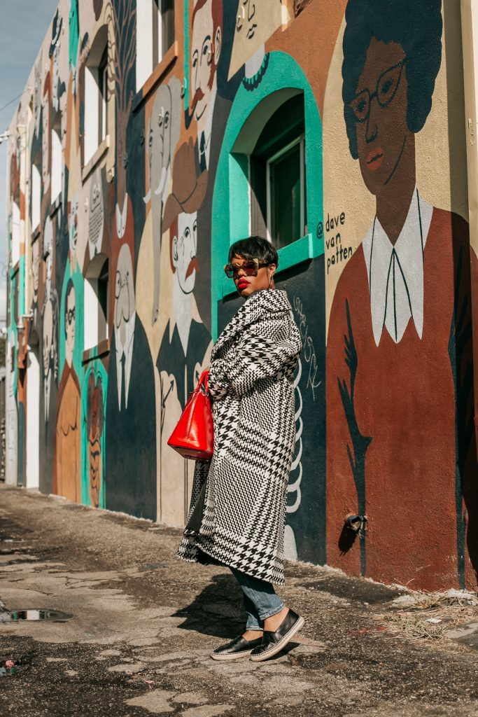 Black woman in black and coat in front of street art in Long Beach, CA