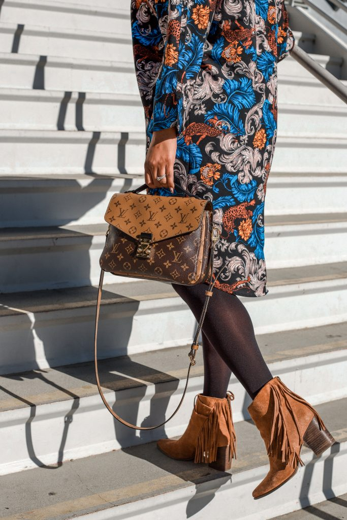 Woman climbs steps in dress from Mango and Louis Vuitton bag.