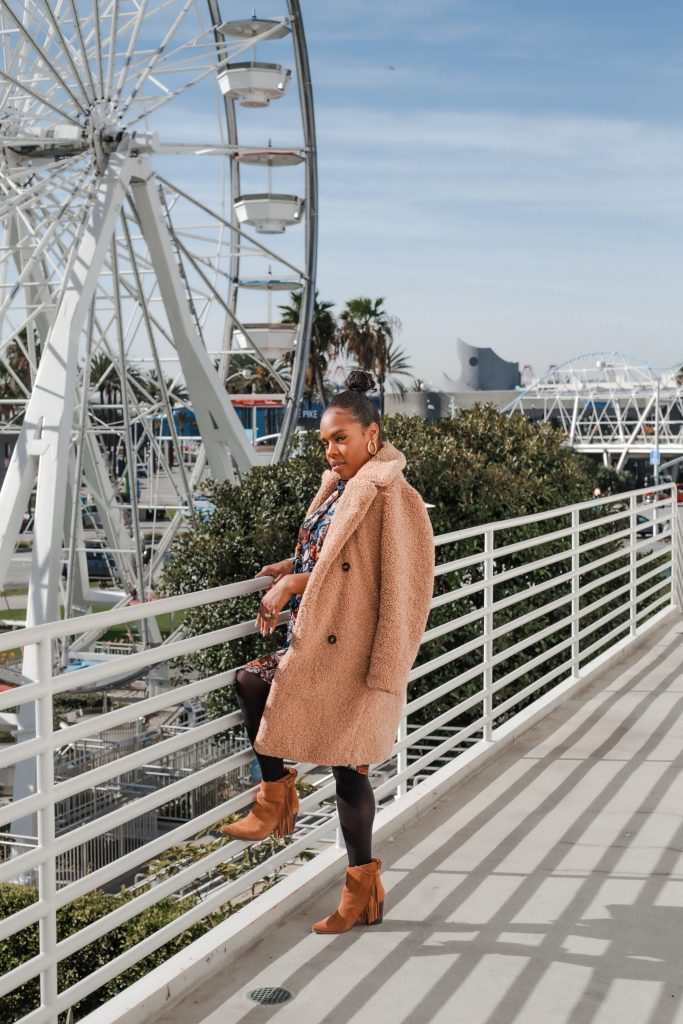 Blogger standing with ferris wheel in the background in California.