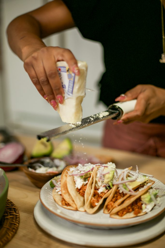 Hautemommie grates cotija cheese over the chorizo tofu tacos.